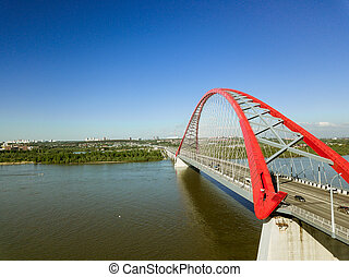 Aerial view of Bugrinsky tiered wide-arch bridge and green trees in Novosibirsk.