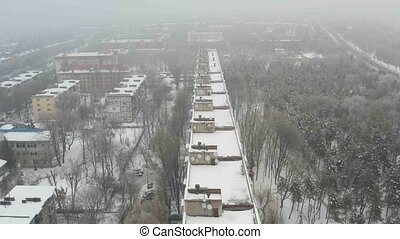 Aerial view of building roof covered with snow. Winter foggy...