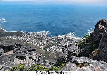 aerial view of Camps Bay and coastline against blue ocean from Table Mountain in Cape Town, South Africa