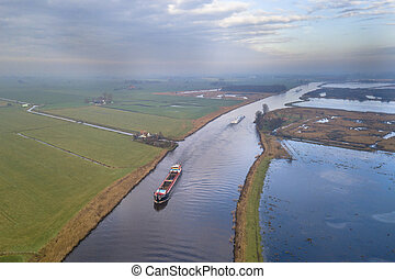 Aerial view of canal in Friesland with inland freight ships...