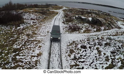 Aerial view of car driving away from shore in winter -...