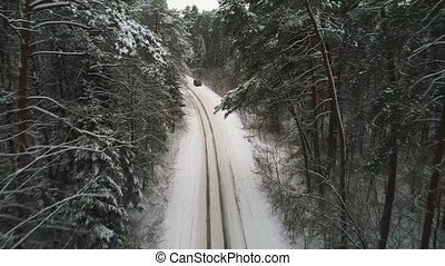 aerial view of car moving in winter forest