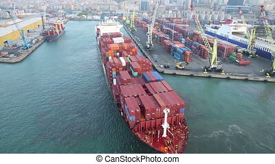 Aerial view of big cargo ship full of containers docking at the pier in the port of Genoa, Italy