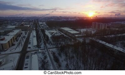 Aerial view of cargo train crossing winter city at sunrise....