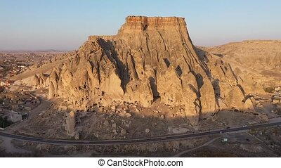Aerial view of castle at Cappadocia, Turkey. Ancient cave dwellings carved into the stone formations. View from above.