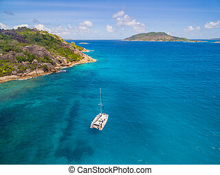 Aerial view of catamaran sailling in coastline. Tropical ...