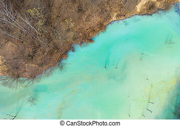Aerial view of chemical residuals flooding a lake from a copper mine exploitation