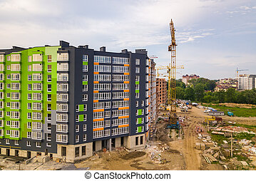 Aerial view of city residential area with high apartment buildings under construction.