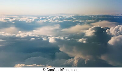 Aerial view of clouds over landscape from airplane.