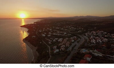 Aerial view of coastal resort town with cottages on the shoreline, Greece