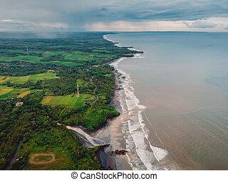 Aerial view of coastline with black sand beach, dirty ocean and waves in Balian, Bali