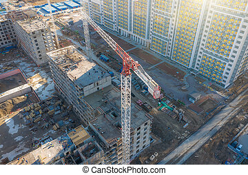 Aerial view of construction cranes and a multi-storey building under construction in a residential area of the city.
