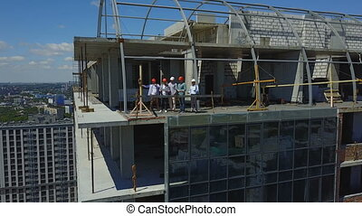 Aerial View Of Construction Site With Team Of Builders On Roof Discussing Plan Of Project