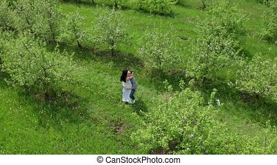 Aerial view of couple among greenery of orchard - Drone shot...