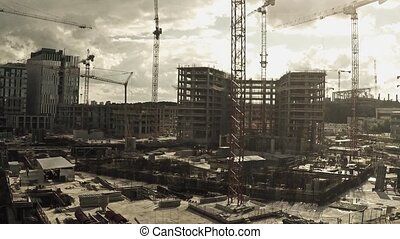 Aerial view of cranes on big construction site of dwelling houses and offices