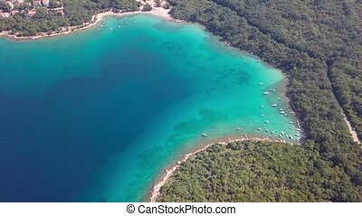 Aerial view of crystal clear water off the coastline inisland with boats Krk, Croatia
