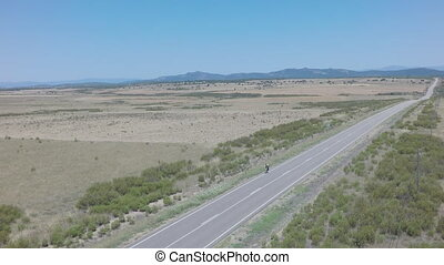 Straight road, cyclist, clear day, blue sky, aerial view, 4K