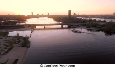 Aerial view of Daugava river in Riga during sunset. City landscape view from the air.