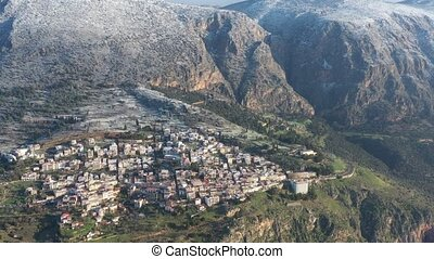 Aerial view of Delphi Greece at sunrise, the Gulf of Corinth, Morning fog over mountains, hoarfrost on roofs, mountainside with layered hills beyond with rooftops in foregroundAerial view of Delphi