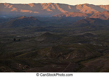 Aerial view of desert mountains at sunset