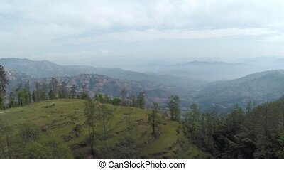 Aerial view of Dhulikhel district in the Kathmandu valley, Nepal. Raven flying close to the drone.