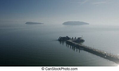 Aerial view of docked motor boat at pier and distant islands...