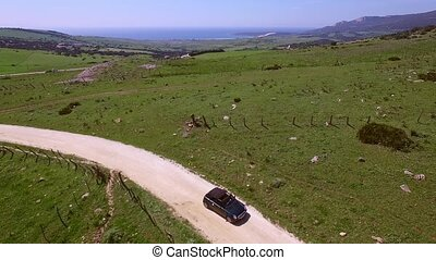 Aerial View Of Driving Car On Hilly Terrain