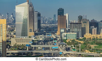 Aerial view of Dubai marina skyscrapers and Internet city towers timelapse with traffic on sheikh zayed road.