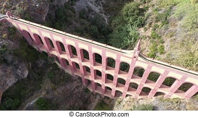 Scenic aerial view of Aqueduct of Eagle, four storied arch bridge over canyon of Barranco de la Coladilla on sunny fall day, Nerja, Spain
