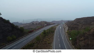 Aerial view of elevated highway with bridge surrounded by dry mountain. Highway with cars and trucks driving both direction. Open road, freeway in dry landscape. Chengde, China.