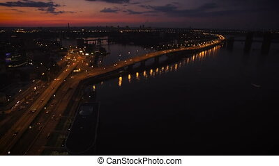 Aerial View of European City at Night with Illuminated Light from Cars, Bridge Over the River. Shot in 4K UHD
