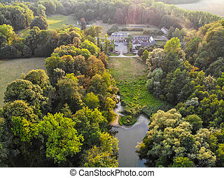 Aerial view of farm style castle surrounded by forest and lake during autumn season and sunset