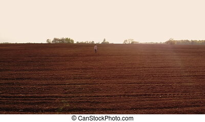 Aerial view of farmer walking through his fields. An adult male farmer in a cap walks across a plowed field and with planted crops in his boots. Top view of a man inspecting the fields. Farmer.