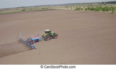 Aerial view of Farming tractor moving on agricultural field...