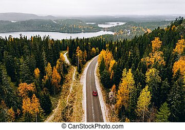 Aerial view of first snowy autumn color forest in the mountains and a road with car in Finland Lapland.