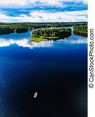 Aerial view of fishing boat in blue lake landscape with green forests on a sunny summer day in Finland.