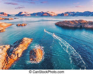 Aerial view of fishing boats, rocks in the blue sea