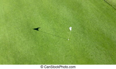Aerial view of flag mark in hole on golf field. Game, entertainment, sport and leisure concept -