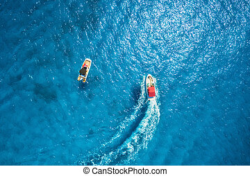 Aerial view of floating motorboat in transparent blue sea
