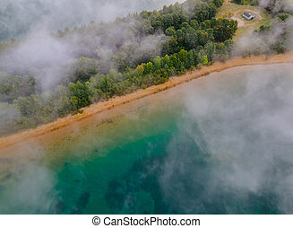Aerial view of foggy trees in colorful sunrise on autumn landscape with forest in low clouds