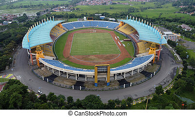 Aerial view of football stadium in Bandung City, Indonesia. Sunset/sunrise and noise cloud. Drone shot. Bandung, Indonesia - 04 22 2021