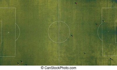 Aerial view of football team practicing at day on soccer...