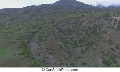 Aerial view of foothills then a vertical pan to reveal...