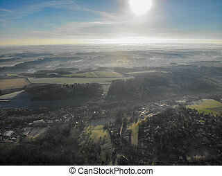 Aerial view of forest and farmland during foggy and cold winter morning with blue sky facing the sun