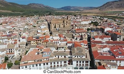 Aerial view of fortified castle and Basilica of Vera Cruz on hill dominating residential areas of Spanish town of Caravaca de la Cruz on summer day. High quality 4k footage
