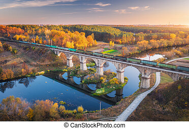 Aerial view of freight train on railroad bridge and river