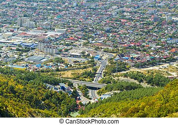Aerial view of Gelendzhik resort city district from hill of caucasian mountains. Buildings and street at the foot of the mountains.