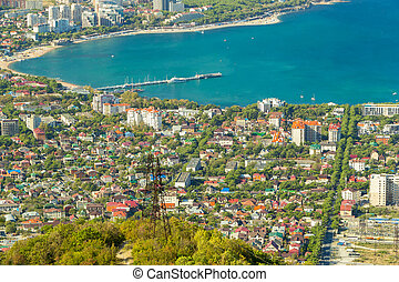 Aerial view of Gelendzhik resort city district from hill of caucasian mountains. Buildings, beaches and blue water of sea bay in frame.
