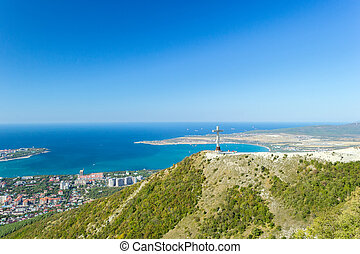 Aerial view of Gelendzhik resort city from hill of caucasian mountains. Worship cross monument on hill.