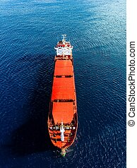 Aerial view of general cargo ship in blue sea. View from above of red empty container ship in the sea.